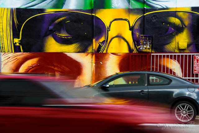 Cars pass in front of a colorful warehouse in Miami, FL