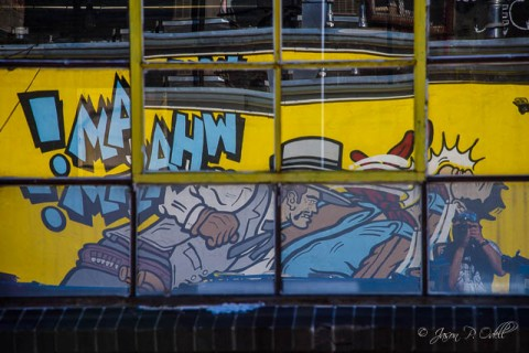 Street art in Denver's RiNo Art District reflected in warehouse windows.